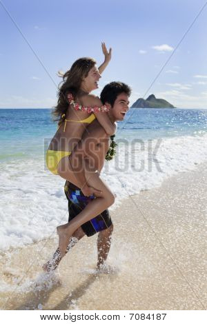 pacific island man carries a young woman on his back
