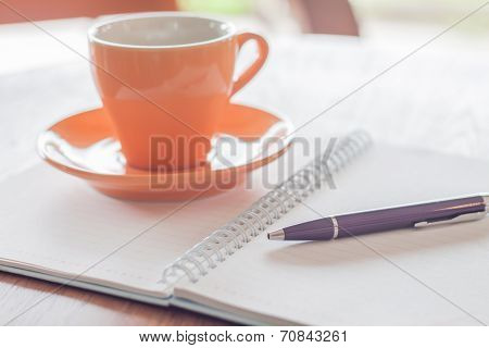 Coffee Cup, Pen And Notebook On Wooden Table