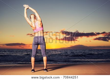 Athletic fitness woman stretching on the beach at sunset
