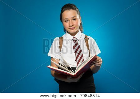 Young schoolgirl with a lovely smile standing in her school uniform facing the camera holding an open book, on blue