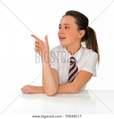 Young schoolgirl pointing to the left of the frame as she draws attention to something she is watching with parted lips, on white