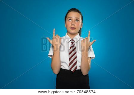 Attractive schoolgirl pointing above her head with both hands while looking up in the same direction, on blue