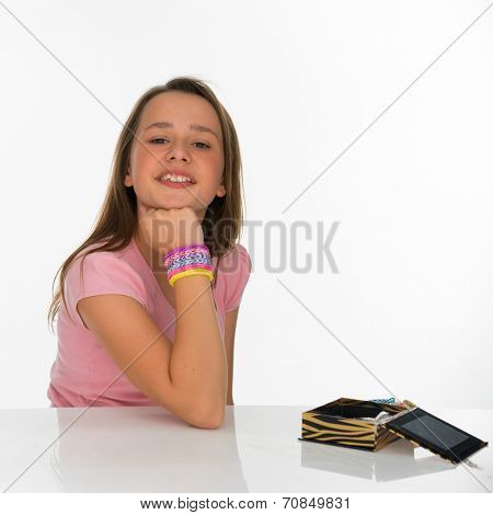 Beautiful young girl in makeup and jewellery sitting with her jewellery box in front of her smiling happily at the camera with a friendly smile