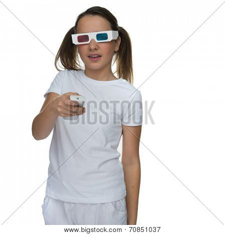 Young girl with her hair in pigtails wearing 3d stereoscopic glasses and holding a remote control for a video or film, ioslated on white
