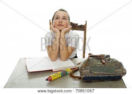 Young schoolgirl hoping for an answer sitting at her desk with her textbooks and backpack staring hopefully up into the air, on white