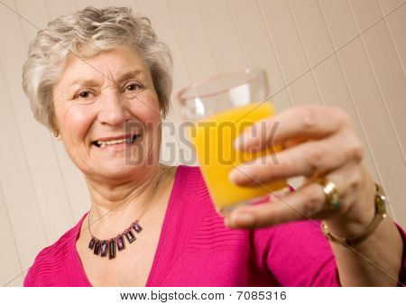 Mature Older Lady With Glass Of Orange Juice