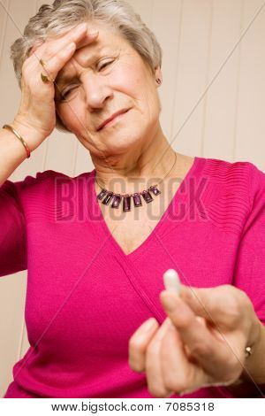Senior Older Lady With Headache Holding Tablet Or Pill