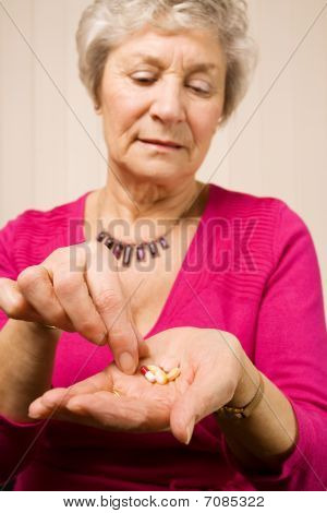 Mature Older Woman Taking A Tablet Or Pill