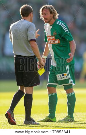 VIENNA, AUSTRIA - JULY 12 Harald Pichler (#27 Rapid) argues with referee Harald Lechner (Austria) at a friendly soccer game on July 12, 2013 in Vienna, Austria.