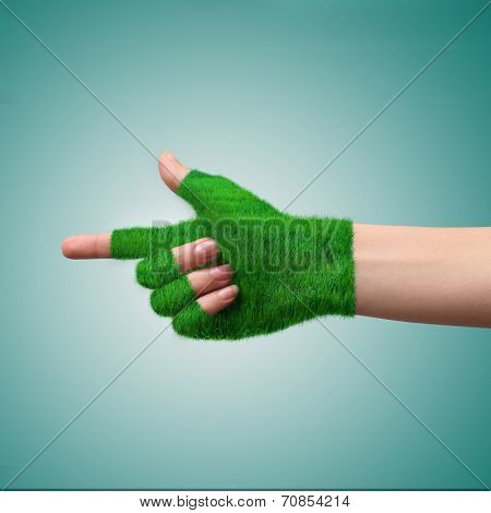 Go Green Concept Hand in glove grass indicates the direction. Ecological concept.