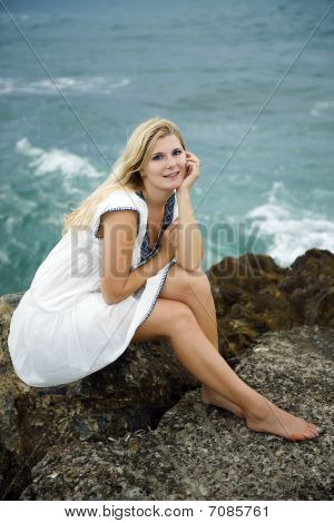 Young Beautiful Fresh Woman Sitting On A Stone Near The Blue Stormy Sea