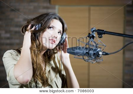 Young Beautiful Retro Woman Recording The Sound In Professional Studio With Mic And Phones. Indoor