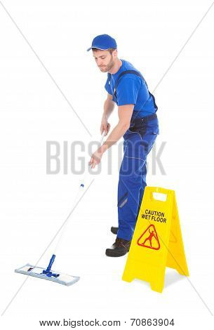 Male Servant Mopping Floor By Wet Floor Sign