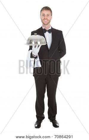 Portrait Of Confident Waiter Holding Domed Tray