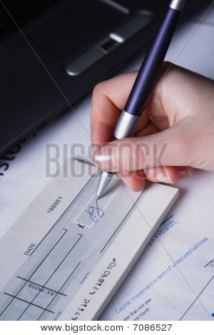 A Woman's Hand Signing A Check