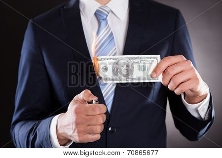 Midsection Of Businessman Burning Money
