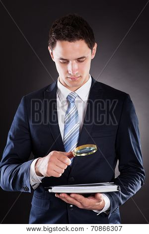 Businessman Analyzing Documents With Magnifying Glass