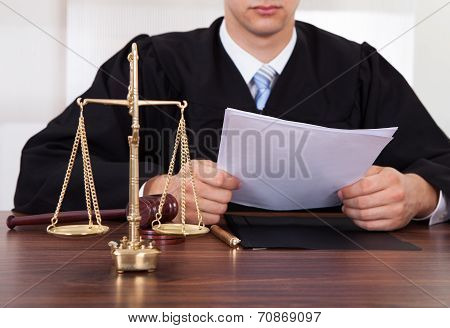 Judge Reading Document At Table In Courtroom