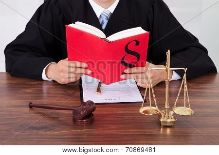 Judge Reading Book At Table In Courtroom