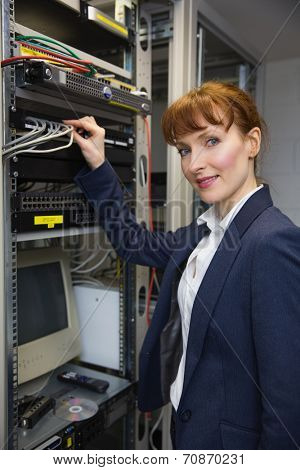 Pretty computer technician smiling at camera while fixing server in large data center