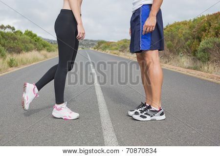 Side view low section of fit young couple standing on the open road together