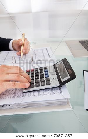 Businessman Holding Calculating Expense In Office