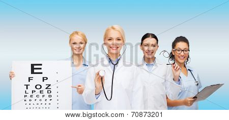 healthcare, vision and medicine concept - smiling female eye doctors and nurses with eye exam chart, glasses and clipboard