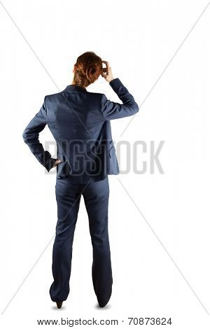 Businesswoman in suit scratching head on white background