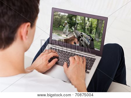 Man Playing Action Game On Laptop At Home