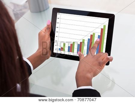 Businesswoman Analyzing Comparison Graph On Digital Tablet At Desk