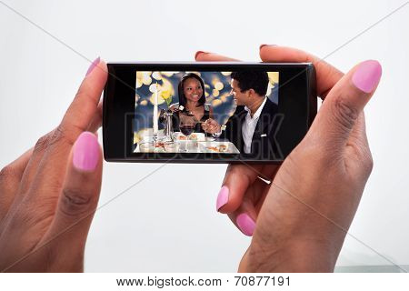 Woman Watching Video On Mobile Phone At Home
