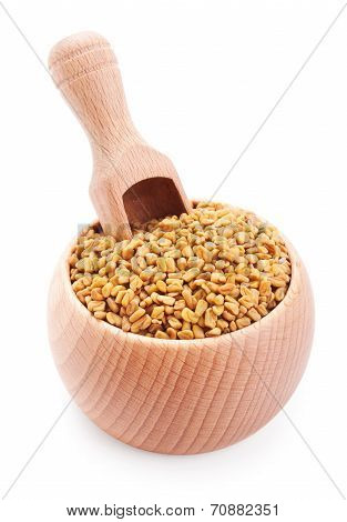 Wooden Scoop In Bowl Full Of Fenugreek Isolated On White