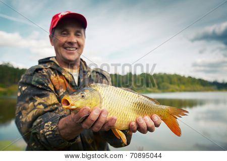 Happy smiling fisherman holding his trophy carp (Cyprinus carpio) with pond on the background. Focus on the fish
