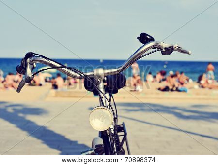closeup of a bicycle parked on the seafront with people on the beach in the background, with a filter effect