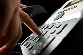picture of keypad  - Person dialing out on a landline telephone punching in the numbers on the keypad with a finger closeup side angle view on a dark background - JPG
