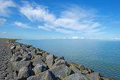 pic of dike  - Dike of rocks and basalt along a lake in summer - JPG