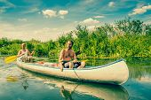 foto of canoe boat man  - Exhausted Men Sailing In A Canoe At Summertime - JPG