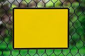 stock photo of chicken-wire  - Blank yellow info plate hung on a wire fence - JPG