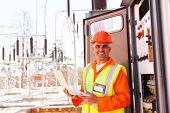 stock photo of substation  - senior technician holding laptop in front of transformer at substation - JPG