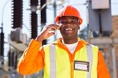 picture of substation  - happy african electrician using cell phone in electric substation - JPG