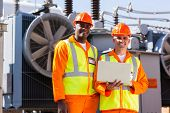 picture of transformer  - portrait of happy electrical engineers with laptop in front of transformer - JPG