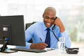 pic of writing  - happy african businessman talking on landline phone and writing report - JPG