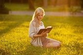 stock photo of beatitudes  - Blonde girl sitting on the grass and reading a book - JPG
