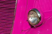 stock photo of headlight  - Closeup detail of the headlight of an antique car painted pink - JPG