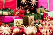 picture of gift wrapped  - Plenty of small Christmas presents piled up before larger wrapped gifts in the rear - JPG