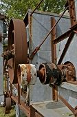 image of pulley  - A side view of an old threshing machine displays several pulleys with much usage - JPG