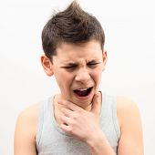 stock photo of larynx  - teenager suffering from a sore throat on a light background - JPG