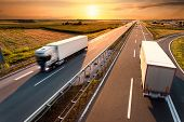picture of truck  - Two trucks on highway in motion blur at sunset - JPG
