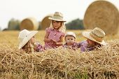 picture of haystack  - a young family on haystacks in cowboy hats - JPG