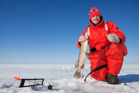 image of ice fishing  - Happy ice fisherman holding a northern pike caught on a tip up - JPG